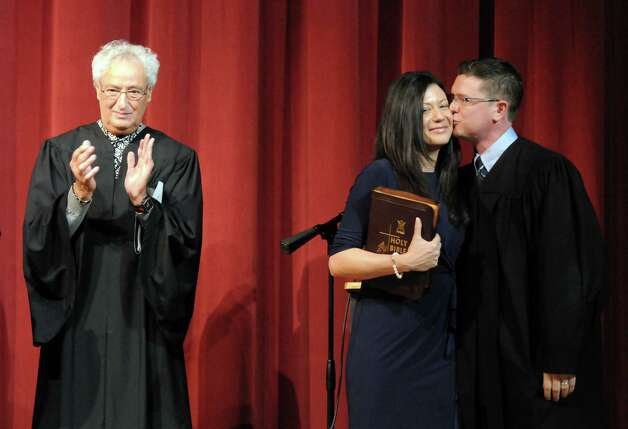 Schenectady County Court Judge Matt Sypniewski, right, gives his wife Diane a kiss after taking his oath of office from Judge Barry Kramer, left, Friday, Jan. 9, 2015, at Schenectady High School in Schenectady, N.Y. Both Judges Kramer and Sypniewski are graduates of Schenectady High School. (Michael P. Farrell/Times Union) Photo: Michael P. Farrell / 00030123A