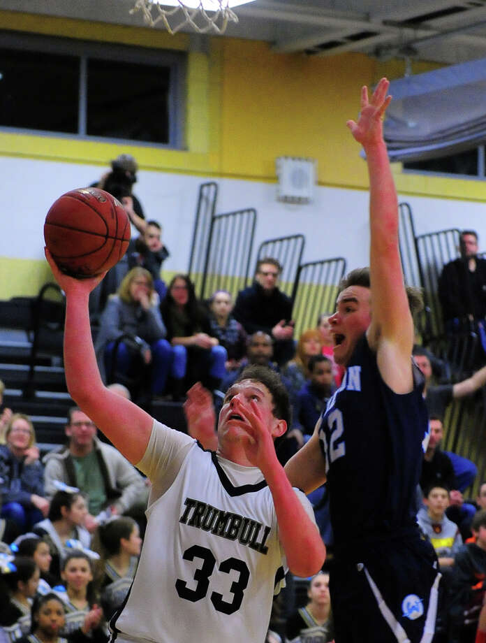 Trumbull's Ben McCullough looks for two under the hoop as Wilton's Matt Shifrin defends, during basketball action in Trumbull, Conn., on Friday Jan. 9, 2015. Photo: Christian Abraham / Connecticut Post