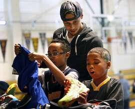 Golden State Warriors' Stephen Curry watches as Make-A-Wish participants Cash Banks (right) and Aubrey Terry open a gift bag from Curry after the unveiling of Curry's new Under Armour shoe at St. Joseph Notre Dame High School in Alameda, Calif. on Thursday, January 8, 2015.