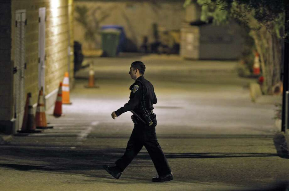 A San Francisco police officer walks through a parking lot at the Mission Station after an officer-involved shooting there. Photo: Carlos Avila Gonzalez / Associated Press / San Francisco Chronicle