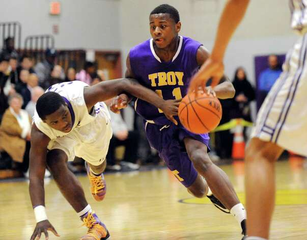 Troy's Dyaire Holt, center, drives up court as CBA's Taurian Taylor defends during their basketball game on Friday, Jan. 9, 2015, at Christian Brothers Academy in Colonie, N.Y. (Cindy Schultz / Times Union) Photo: Cindy Schultz / 00030125A