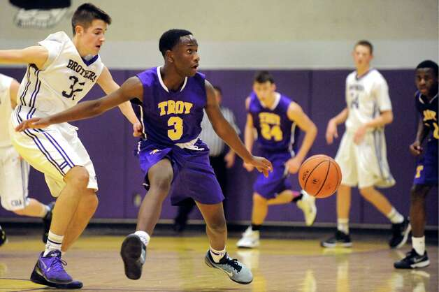 Troy's Darius Holmes-Hines, center, and CBA's Andrew Evans, left, put on the brakes as they chase a loose ball during their basketball game on Friday, Jan. 9, 2015, at Christian Brothers Academy in Colonie, N.Y. (Cindy Schultz / Times Union) Photo: Cindy Schultz / 00030125A