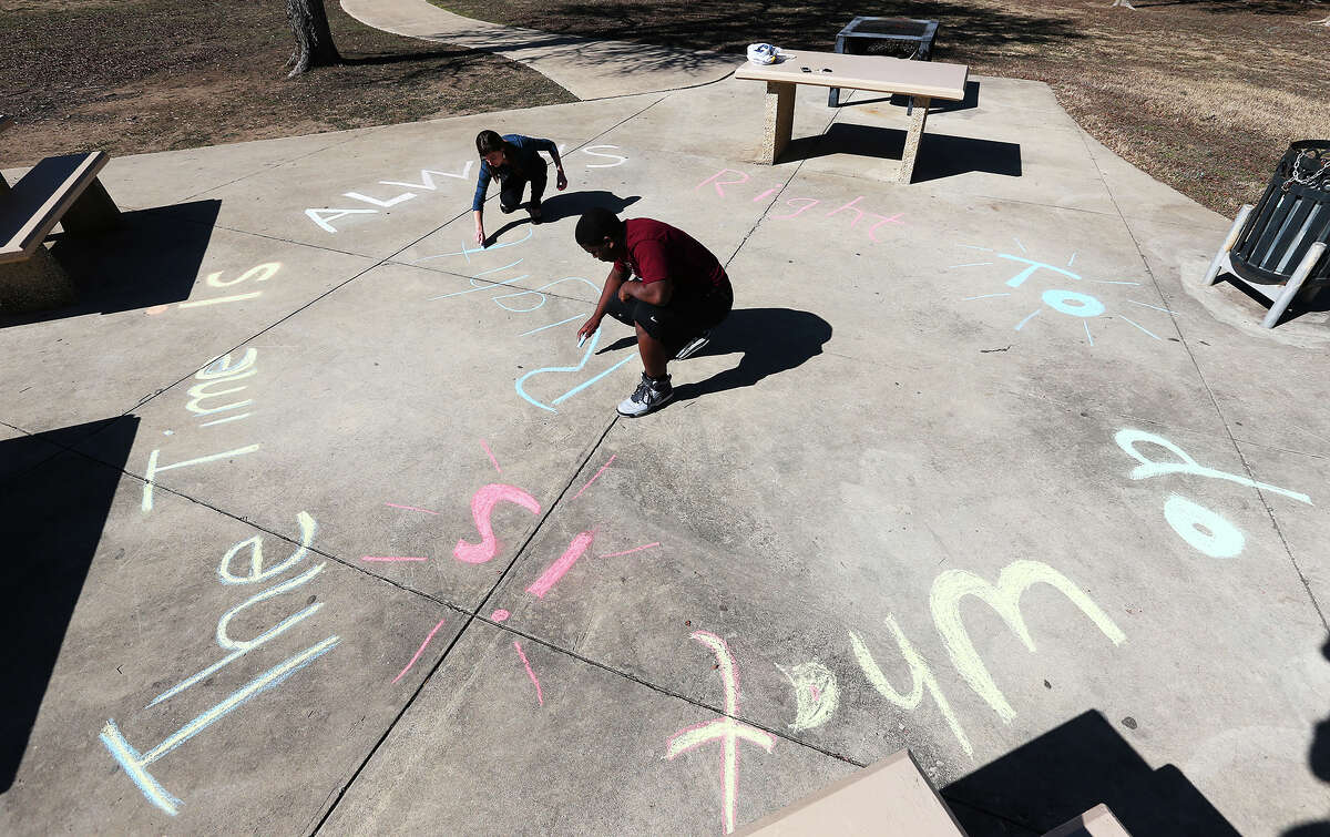 Michelle Bartonico and Christopher Williams work on a Martin Luther King Jr. quote chalking at MLK Park last year.