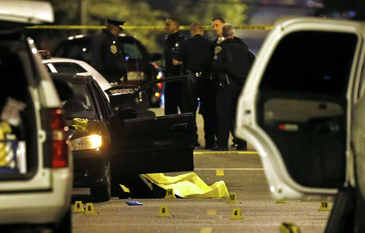 A car sits at the scene of a quadruple homicide on Laguna Street near Page Street in San Francisco on Friday.