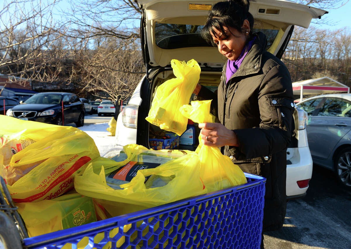 Veronica Foncello, of Shelton loads up her vehicle with groceries at the Shop Rite in Shelton, Conn., on Saturday Jan. 10, 2015. The state is considering a ban on plastic bags like the ones in the cart. If outlawed buyers would be forced to either bring their own bags or pay for store paper bags.