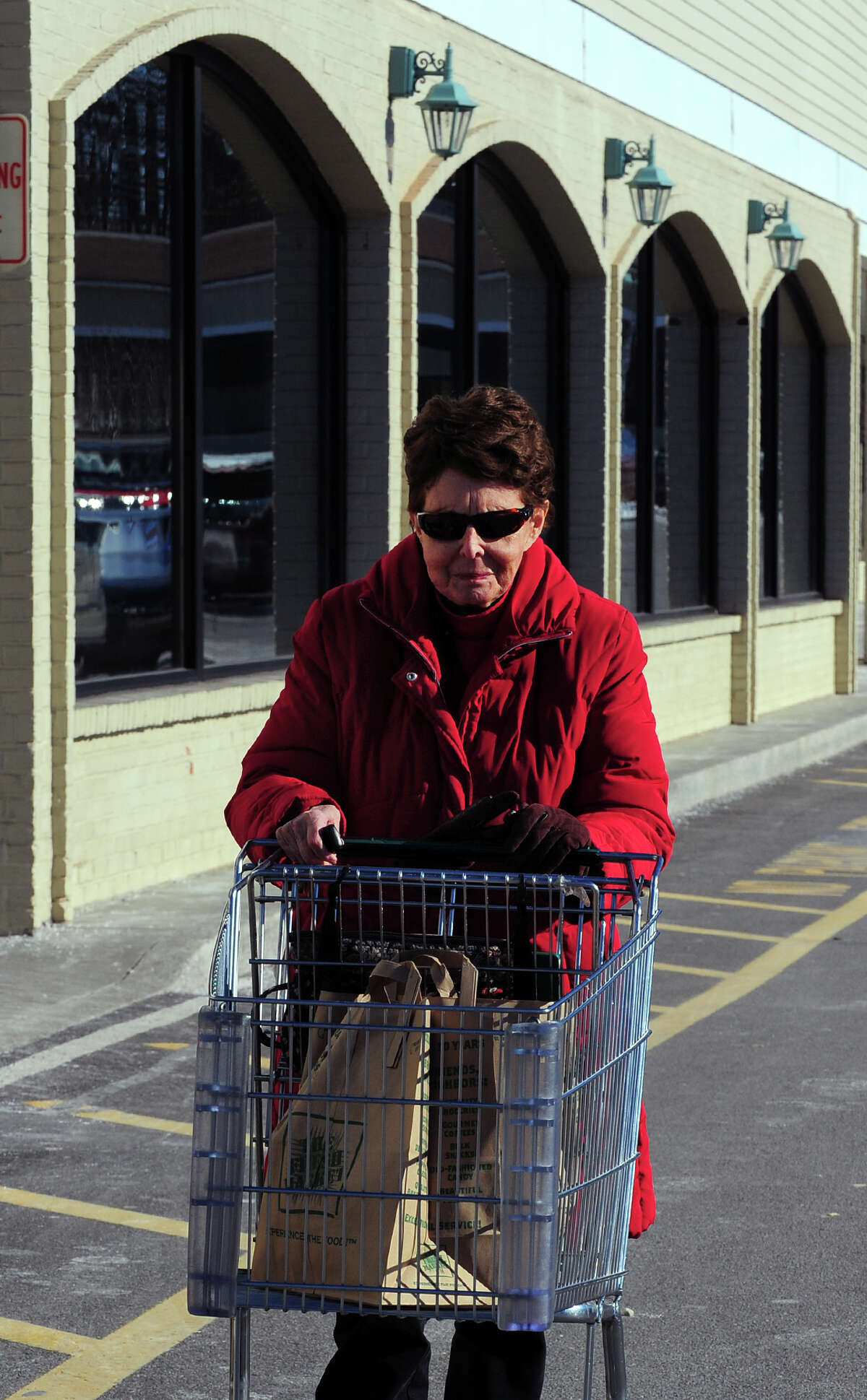 Florence Josem, of Norwalk, walks to her vehicle with groceries at The Fresh Market in Westport, Conn., on Saturday Jan. 10, 2015. The state is considering a ban on plastic bags. The Fresh Market has already stopped using them in its store. If outlawed buyers would be forced to either bring their own bags or pay for store paper bags.