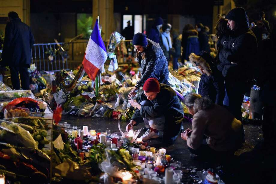People light candles at a memorial near the Paris offices of satirical magazine Charlie Hebdo, site of a deadly attack last week. Photo: Jeff J Mitchell / Getty Images / 2015 Getty Images