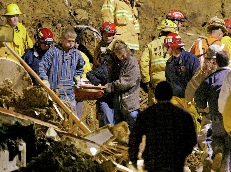 Residents and rescue workers carry the body of a child found after a landslide that killed 10 in the seaside town of La Conchita in Ventura County in 2005. Photo: Damian Dovarganes / Associated Press / AP
