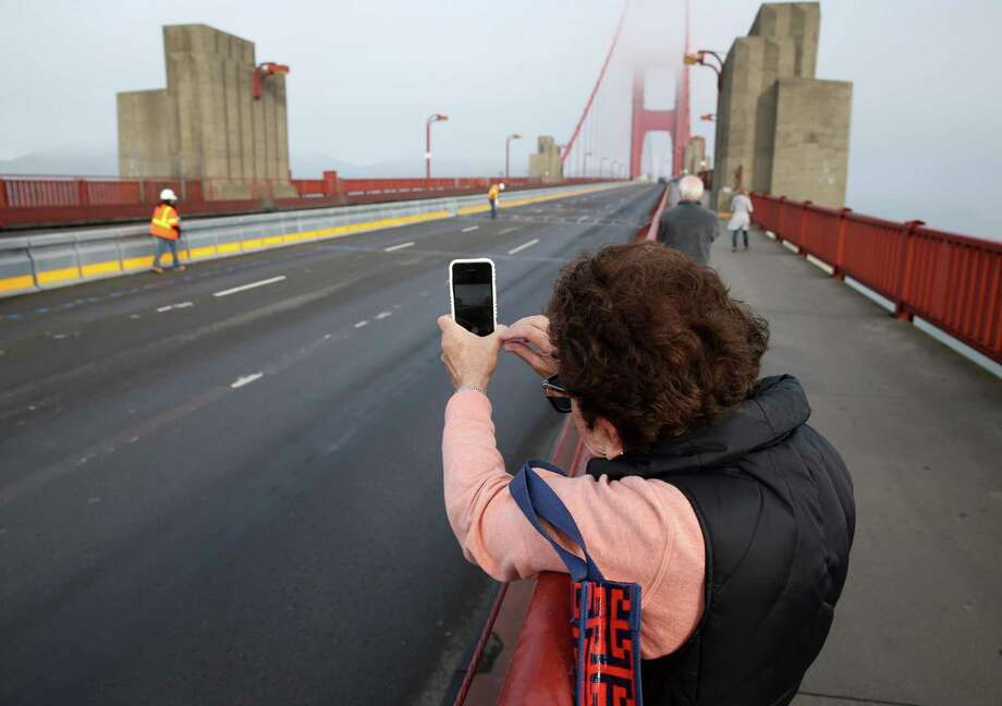 Lynn Bloom snaps a photo of a road crew installing the movable median barrier on the Golden Gate Bridge in San Francisco, Calif. on Saturday, Jan 10, 2015. Photo: Paul Chinn / The Chronicle / ONLINE_YES