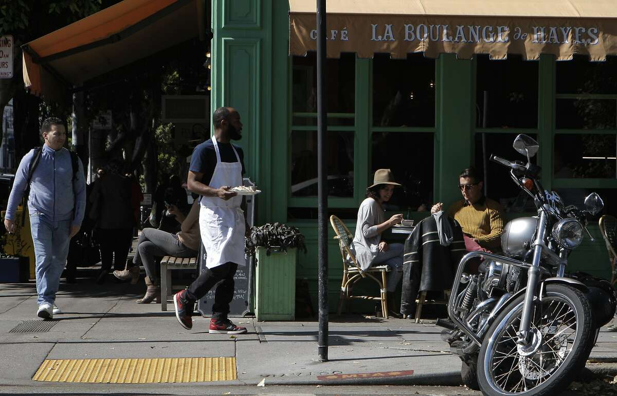 Lorena Cortez, center, wearing the hat, and David Vel, in the sand colored sweater, enjoys a street side lunch at La Boulange de Hayas in Hayes Valley in San Francisco, Calif., on Friday October 10, 2014.