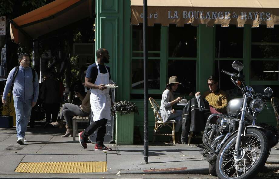 Lorena Cortez, center, wearing the hat, and David Vel, in the sand colored sweater, enjoys a street side lunch at La Boulange de Hayas in Hayes Valley in San Francisco, Calif., on Friday October 10, 2014. Photo: Daniel E. Porter, The Chronicle