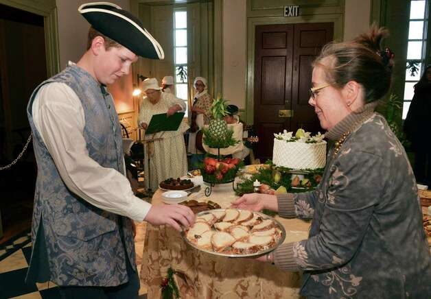 Philip Panzera, left, 13, of Cobleskill, is offered a slice of King's cake by Schuyler Mansion staff member Debbie Rerezduring their annual Twelfth Night festivities at the Schuyler Mansion Saturday Jan. 10, 2015, in Albany, NY.  (John Carl D'Annibale / Times Union) Photo: John Carl D'Annibale / 00030135A