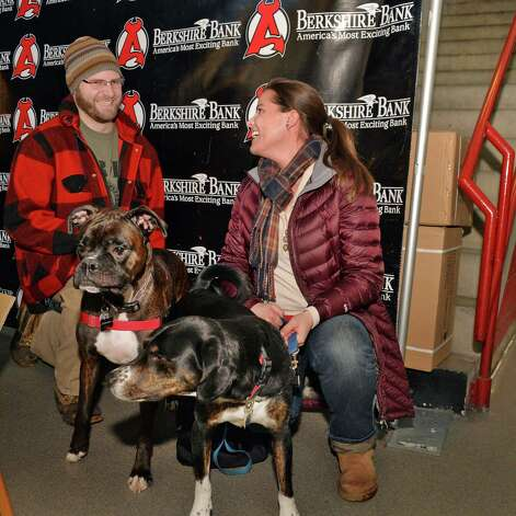 Nick Pisani, left, of Berlin and his dog Guinness and Lisa Hoerz of Rotterdam and her dog Laker during the fifth annual OPucks and PawsO night at Times Union Center as fans bring their dogs to watch the Bridgeport Sound Tigers battle the Albany Devils  Saturday Jan. 10, 2015, in Albany, NY.  (John Carl D'Annibale / Times Union) Photo: John Carl D'Annibale / 00030087A