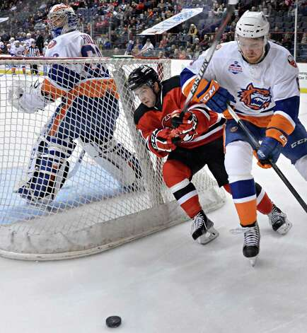 Bridgeport Sound Tigers goalie Kevin Poulin, left, watches as Albany Devils' #9 Joe Whitney, center, and Bridgeport's #8 Griffen Reinhart chase the puck during Saturday's game at the Times Union Center Jan. 10, 2015, in Albany, NY.  (John Carl D'Annibale / Times Union) Photo: John Carl D'Annibale / 00030124B
