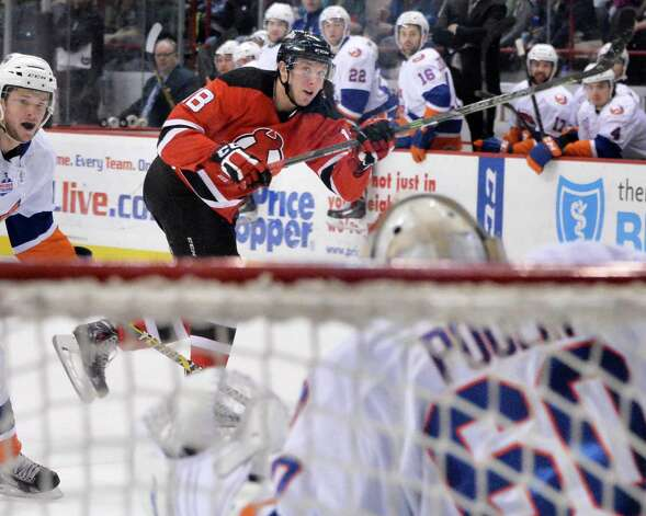 Albany Devils' #18 Stefan Matteau, center, takes a shot on goal against Bridgeport Sound Tigers goalie Kevin Poulin during Saturday's game at the Times Union Center Jan. 10, 2015, in Albany, NY.  (John Carl D'Annibale / Times Union) Photo: John Carl D'Annibale / 00030124B