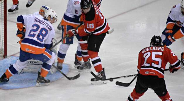 Albany Devils' #25 David Wohlberg, right, scores against Bridgeport Sound Tigers during Saturday's game at the Times Union Center Jan. 10, 2015, in Albany, NY.  (John Carl D'Annibale / Times Union) Photo: John Carl D'Annibale / 00030124B