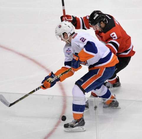 Bridgeport Sound Tigers' #2 Jesse Graham, left, and Albany Devils' #9 Joe Whitney tangle during Saturday's game at the Times Union Center Jan. 10, 2015, in Albany, NY.  (John Carl D'Annibale / Times Union) Photo: John Carl D'Annibale / 00030124B