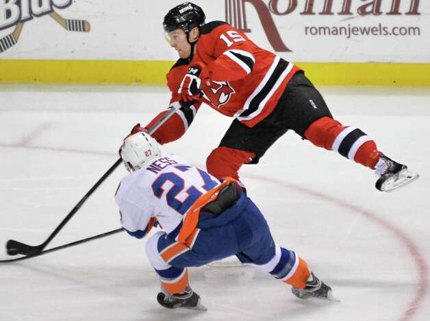 Albany Devils' #15 Paul Thompson, top, gets a shot past  Bridgeport Sound Tigers' #27 Aaron Ness during Saturday's game at the Times Union Center Jan. 10, 2015, in Albany, NY.  (John Carl D'Annibale / Times Union) Photo: John Carl D'Annibale / 00030124B