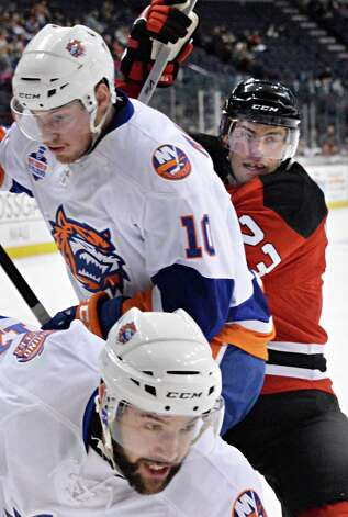 Albany Devils' #23 Darcy Zajac, right, takes Bridgeport Sound Tigers #10 Scott Mayfield and #17 Colton Gilles, bottom to boards during Saturday's game at the Times Union Center Jan. 10, 2015, in Albany, NY.  (John Carl D'Annibale / Times Union) Photo: John Carl D'Annibale / 00030124B