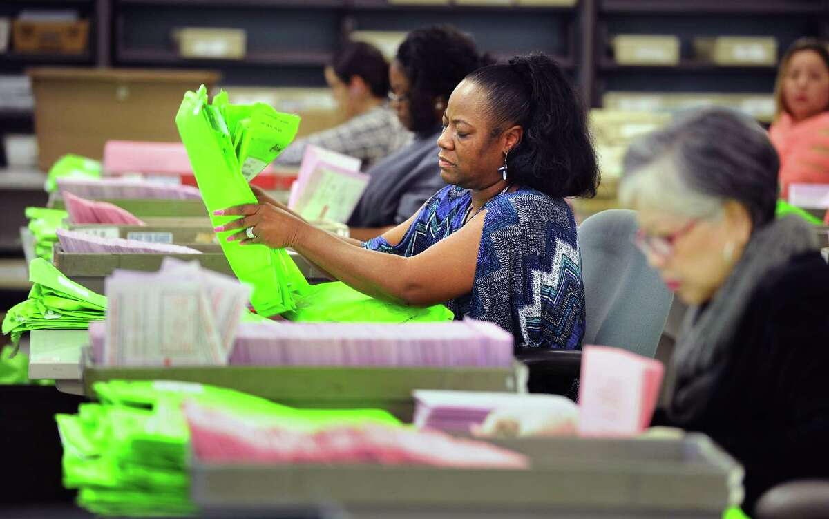 In November, workers count mail-in and absentee ballots at the Los Angeles County registrar's office. The county is struggling to remedy low voter turnout.