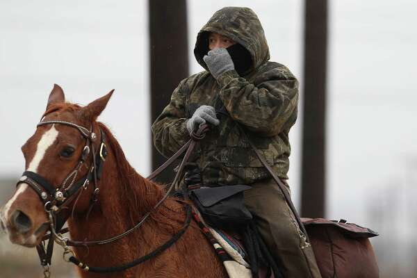 A.J. Reyna covers himself from the cold while riding in Sacred Heart Church's 32nd Annual Trailride on Saturday, Jan. 10, 2015. Despite bouts of freezing temperatures and rain about 20 riders bundled up, strapped on their boots and saddled their horses for a trek through Southwest Bexar County as a fundraiser for the church's Children Faith Formation program. The day-long ride concluded with a dinner and a dance. (Kin Man Hui/San Antonio Express-News)