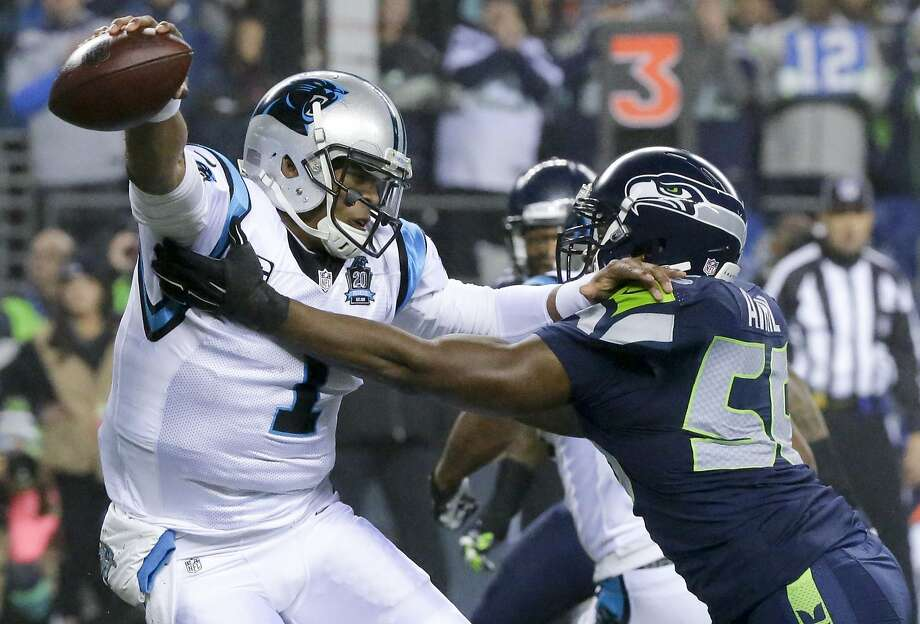 Seattle Seahawks defensive end Cliff Avril, right, applies pressure to Carolina Panthers quarterback Cam Newton during the first half of an NFL divisional playoff football game in Seattle, Saturday, Jan. 10, 2015. (AP Photo/Ted S. Warren) Photo: Ted S. Warren, Associated Press