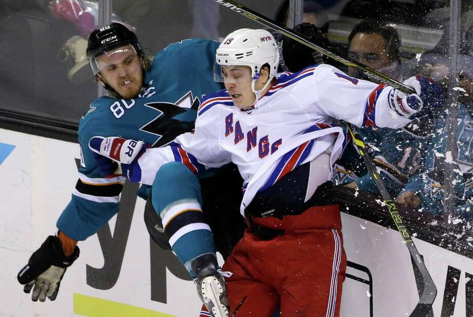 The Sharks' Matt Tennyson and Rangers' Jesper Fast collide along the boards during the second period of New York's 3-1 victory. San Jose has lost three in a row at SAP Center after an eight-game home win streak. Photo: Marcio Jose Sanchez / Associated Press / AP