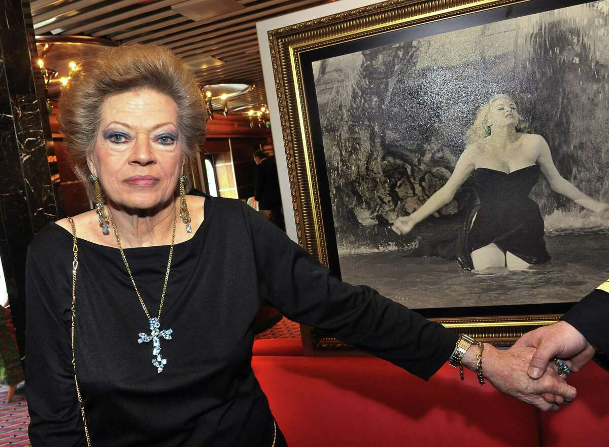 """(FILES) - A picture taken on June 21, 2010 shows Swedish-born film star Anita Ekberg posing aboard the Italian cruise ship Costa Atlantica at quay in Stockholm next to a picture showing her her famous swim in the Trevi fountain in """"La Dolce Vita"""" by Italian director Federico Fellini in 1960. Anita Ekberg died near Rome, aged 83, media reports say on January 11, 2015. AFP PHOTO / JONAS EKSTROMER - SWEDEN OUT - JONAS EKSTROMER/AFP/Getty Images"""