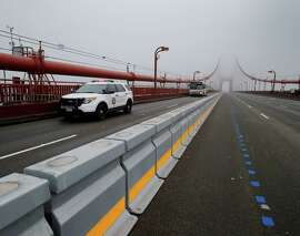 "Golden Gate Transit buses are escorted across the bridge while crews practice moving the barrier with ""zipper"" trucks."