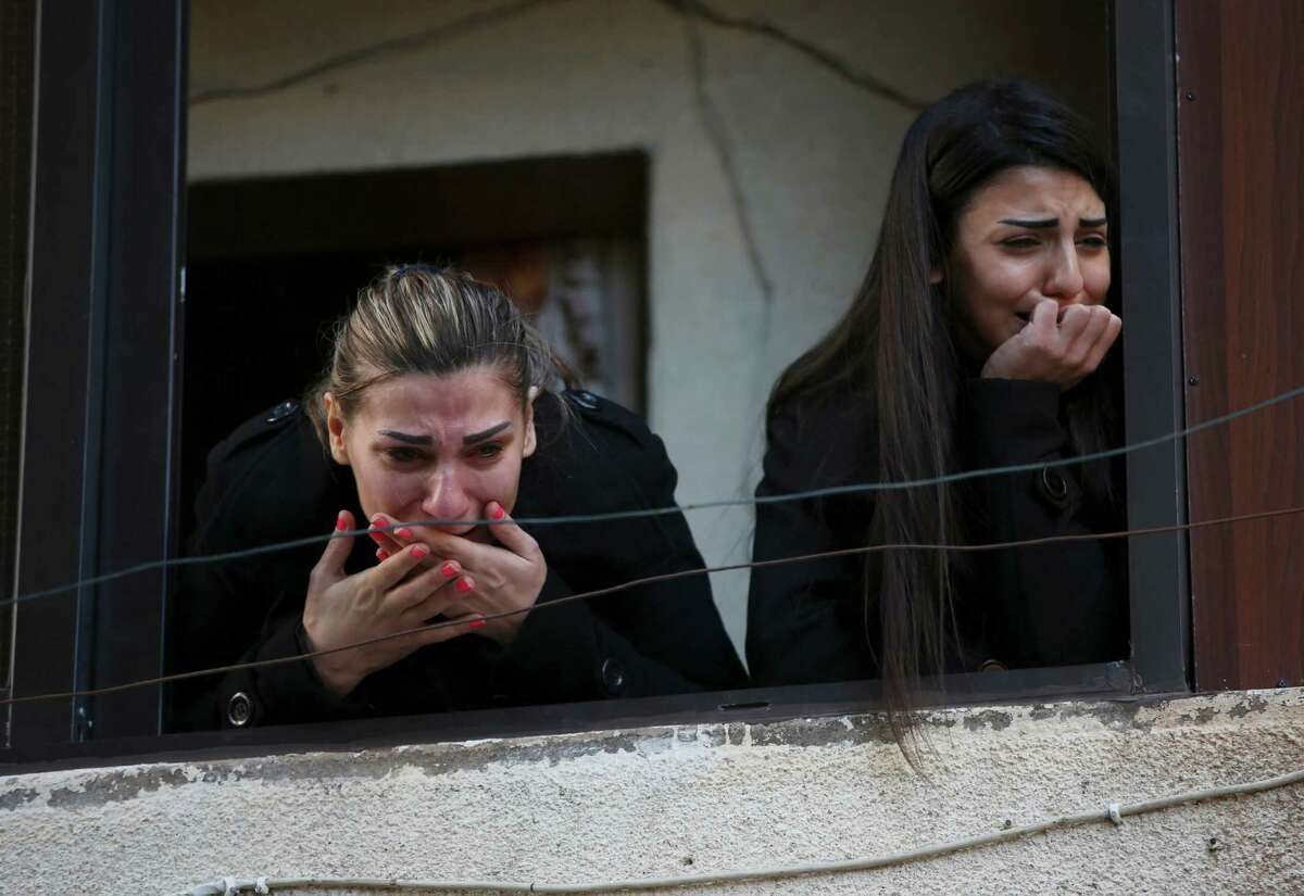 Two Alawite women mourn as they look from a window during the funeral procession of those who were killed in an overnight suicide bombing at a coffee shop in the northern port city of Tripoli, Lebanon, Sunday, Jan. 11, 2015. Syria's al-Qaida-linked Nusra Front claimed responsibility on Twitter for the blast that killed at least seven people and wounded more than 30 in Tripoli's predominantly Alawite neighborhood of Jabal Mohsen.