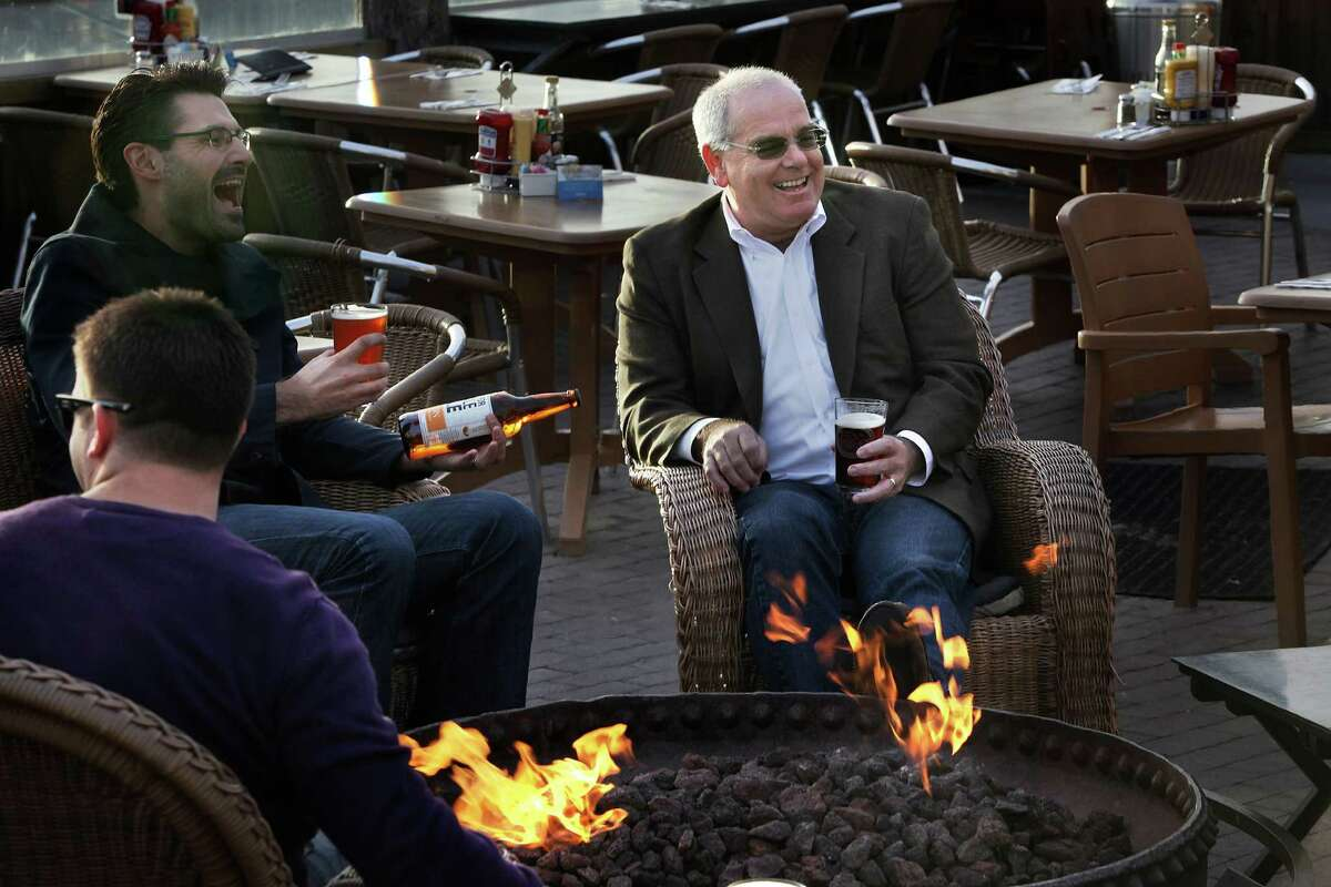 Lenny Mendonca (middle) chats with Mark Wexler (left) of Not for Sale, a global antislavery organization, over beers at Mendonca's Half Moon Bay Brewing Company.