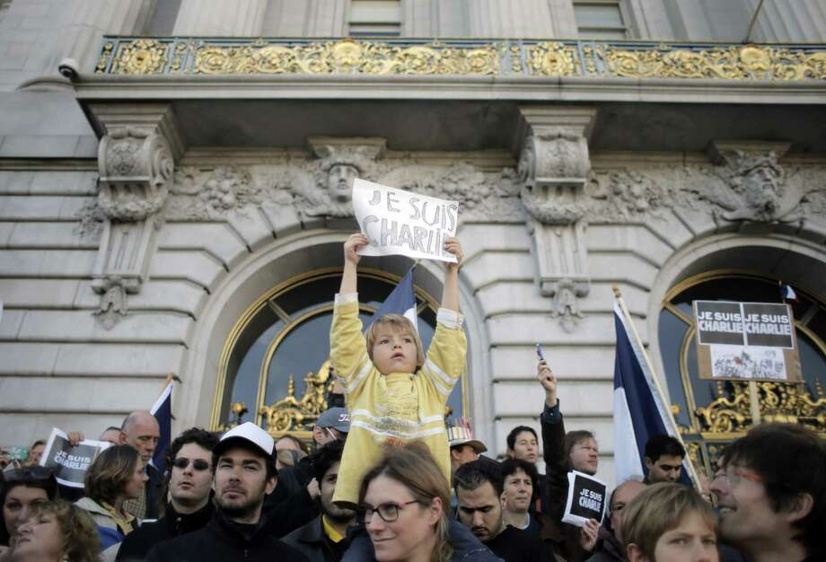 Silvere Castric holds a sign atop mom Juilette Castric's shoulders at S.F. City Hall as about 2,000 people gather Sunday to honor victims of last week's terror attacks in Paris. The sign refers to the Charlie Hebdo attack. Photo: Carlos Avila Gonzalez / The Chronicle / ONLINE_YES