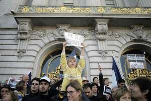 Silvere Castric holds a sign atop mom Juilette Castric's shoulders at S.F. City Hall as about 2,000 people gather Sunday to honor victims of last week's terror attacks in Paris. The sign refers to the Charlie Hebdo attack.