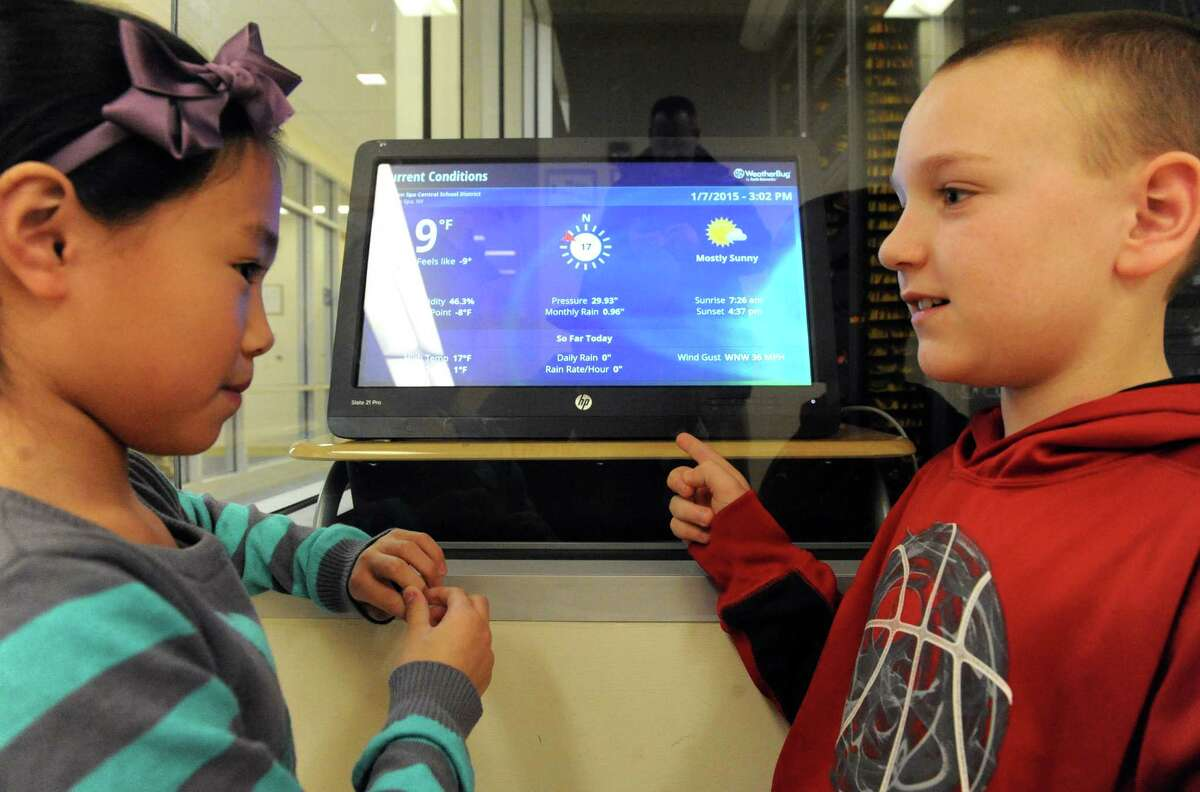 Gordon Creek Elementary School third grade students Emma Ye, left, and Devon Duggan check out the relayed weather data on a display screen hooked to the WeatherBug monitor perched on their schools roof on Wednesday Jan. 7, 2015 in Ballston Spa, N.Y. (Michael P. Farrell/Times Union)