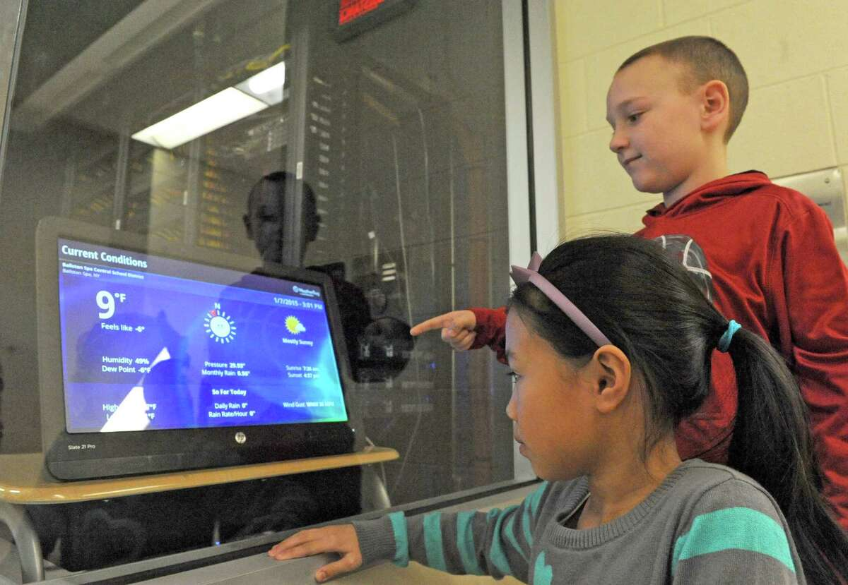 Gordon Creek Elementary School third grade students Emma Ye and Devon Duggan check out the relayed weather data on a display screen hooked to the WeatherBug monitor perched on their schools roof on Wednesday Jan. 7, 2015 in Ballston Spa, N.Y. (Michael P. Farrell/Times Union)