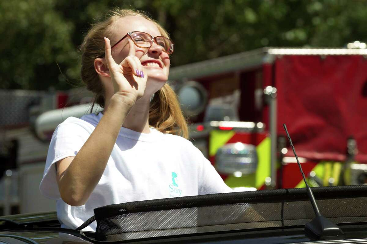 Cassidy Stay gestures to supporters after a memorial celebrating the lives her parents and four siblings at Lemm Elementary School in Spring on July 12.