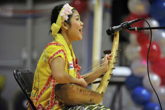 Wa Wa, of Albany, plays a harp instrument as she sings a song her father wrote during a celebration of the Karen New Year at the Albany Boys and Girls Club on Sunday, Jan. 11, 2015, in Albany, N.Y.  The day was filled with traditional music and dance along with talks about the Karen culture and history.  (Paul Buckowski / Times Union) Photo: Paul Buckowski / 00030098A
