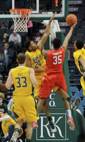 Lavon Long of Siena, left, tries to block the shot of Coleman Johnson of Fairfield during their game at the Times Union Center on Sunday, Jan. 11, 2015, in Albany, N.Y.   (Paul Buckowski / Times Union) Photo: Paul Buckowski / 00030029C