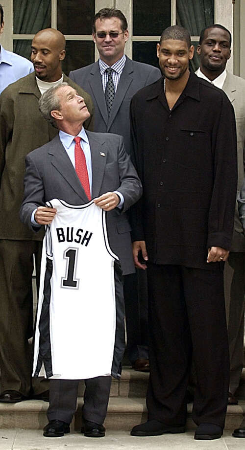President Bush poses for a group photo with the NBA Champion Spurs during a ceremony in the Rose Garden. Left to right are Bruce Bowen, Bush, general manager R. C. Buford, Tim Duncan and Malik Rose. Photo: Gerald Herbert /Associated Press / AP