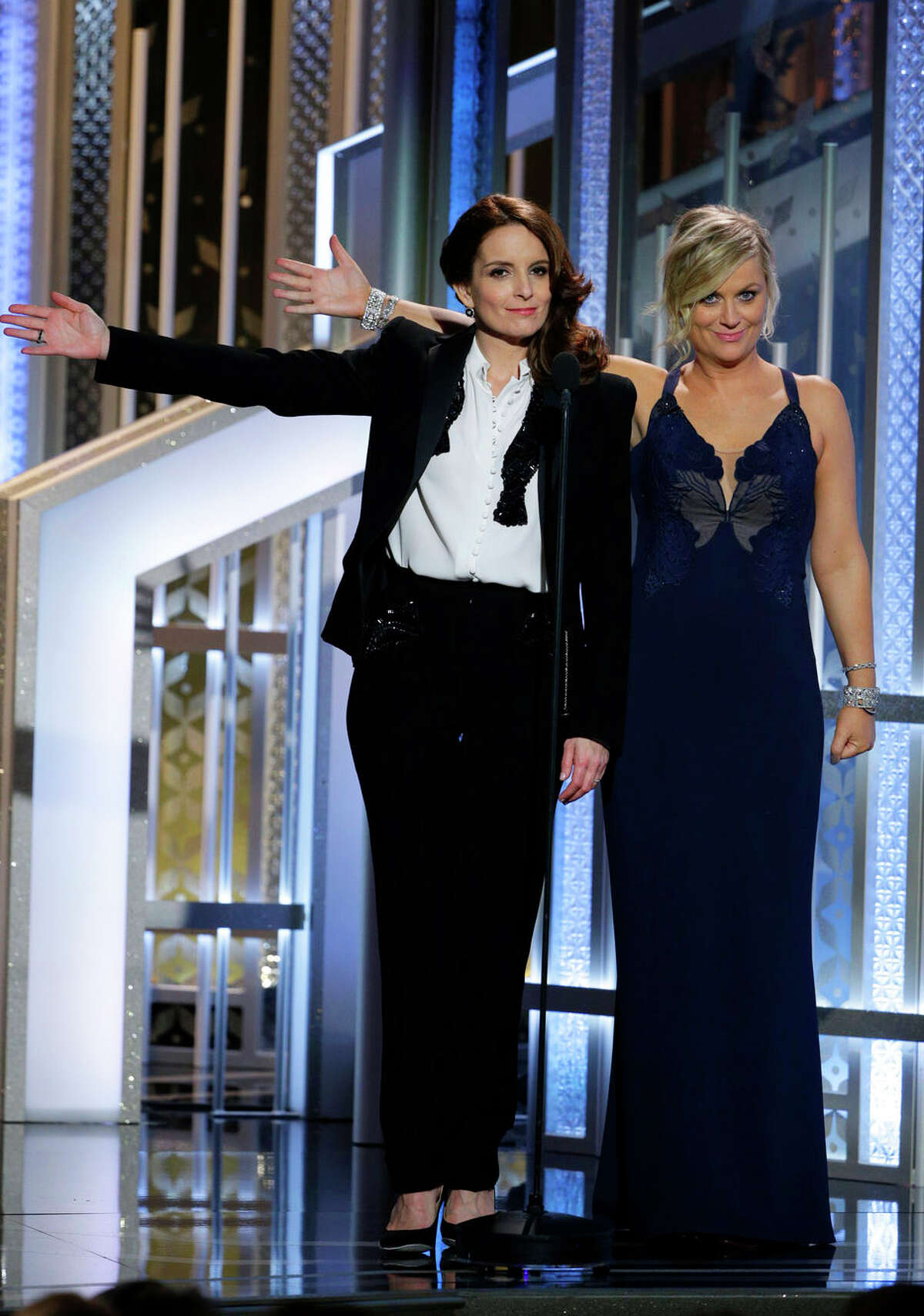 In this image released by NBC, co-hosts Tiny Fey, left, and Amy Poehler introduce Oprah Winfrey at the 72nd Annual Golden Globe Awards on Sunday, Jan. 11, 2015, at the Beverly Hilton Hotel in Beverly Hills, Calif.