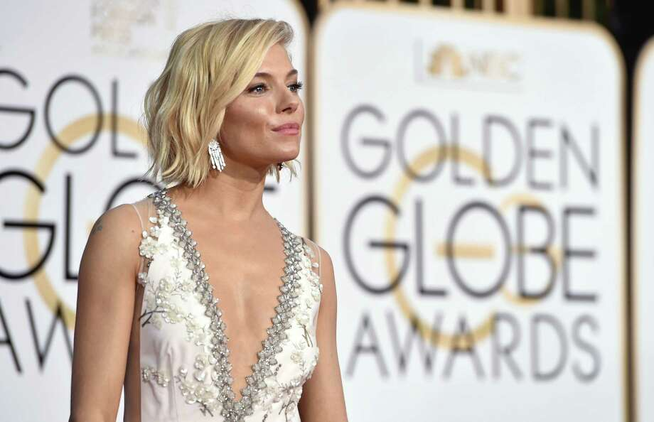 b353c3d1dd Sienna Miller poses in a Miu Miu gown at the 72nd annual Golden Globe  Awards at