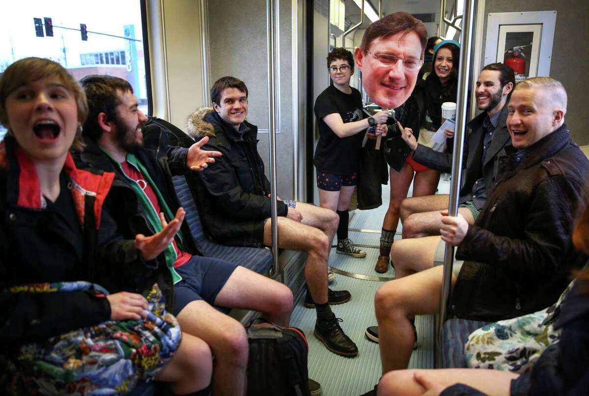 Participants hoist the photo of a man who died recently -after they were asked to do so by passengers that had just attended his wake- during Seattle's 6th annual No Pants Light Rail Ride.