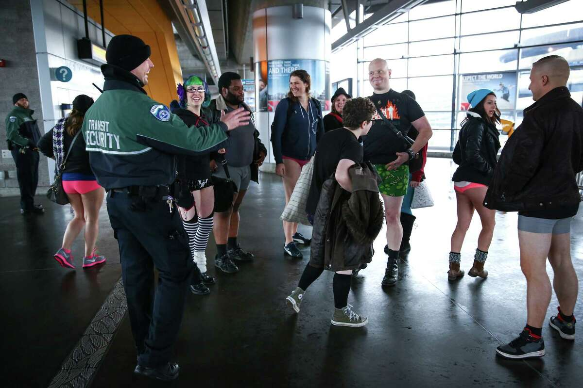 Participants are greeted by Sound Transit security during Seattle's 6th annual No Pants Light Rail Ride. During the quirky annual event, participants strip down to their underwear and ride the rail as if nothing is unusual. They also make stops along the route, often surprising people. Photographed on Sunday, January 11, 2015 in Seattle.