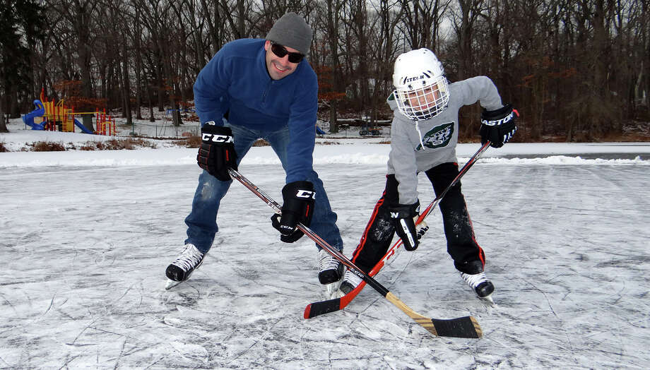 Tim Macklin and son, Max, 9, face off over the puck Sunday at Gould Manor Park. Photo: Mike Lauterborn / Fairfield Citizen