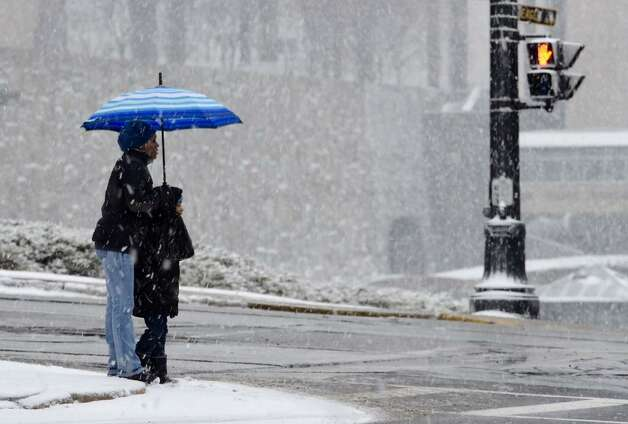 An umbrella shields a pedestrian from the snow in downtown Albany, NY, on Monday, Jan. 12, 2015. (Skip Dickstein/Times Union)