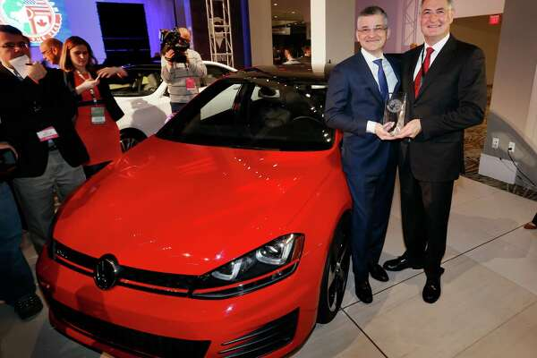 Michael Horn, left, president and CEO of Volkswagen Group of America, Inc., and Heinz-Jakob Neuber, member of the board of management for the Volkswagen brand, hold the trophy for the North American Car of the Year award for the Volkswagen Golf at media previews for the North American International Auto Show in Detroit, Monday, Jan. 12, 2015.