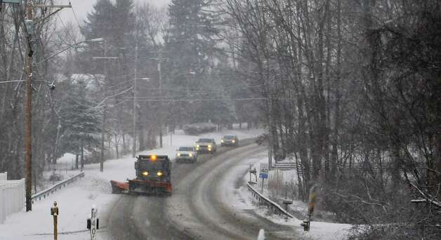A snowplow operator clears the road surface on Albany Shaker Road on Monday morning, Jan. 12, 2015, in Colonie, N.Y.  (Paul Buckowski / Times Union) Photo: Paul Buckowski / 00030160A