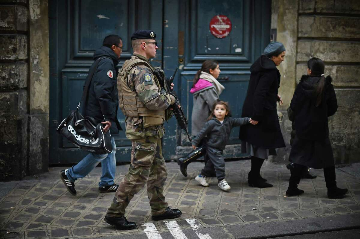 An armed security officer patrols outside a school in the Jewish quarter of the Marais district as children make their way home. Around 4,700 troops are being assigned to protect France's 717 Jewish schools.
