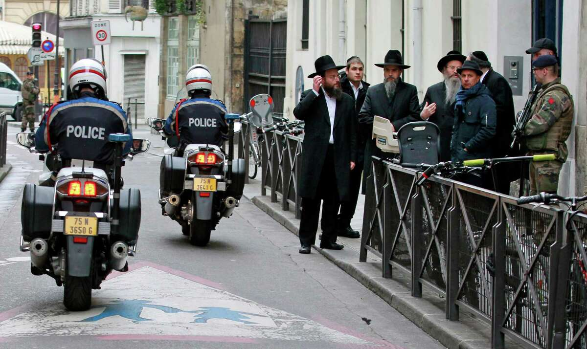 Police officers patrol in front of the Rue Pavee synagogue, in the heart of Paris Jewish quarter, in Paris, Monday Jan. 12, 2015. France on Monday ordered 10,000 troops into the streets to protect sensitive sites after three days of bloodshed and terror, amid the hunt for accomplices to the attacks that left 17 people and the three gunmen dead. (AP Photo/Remy de la Mauviniere)