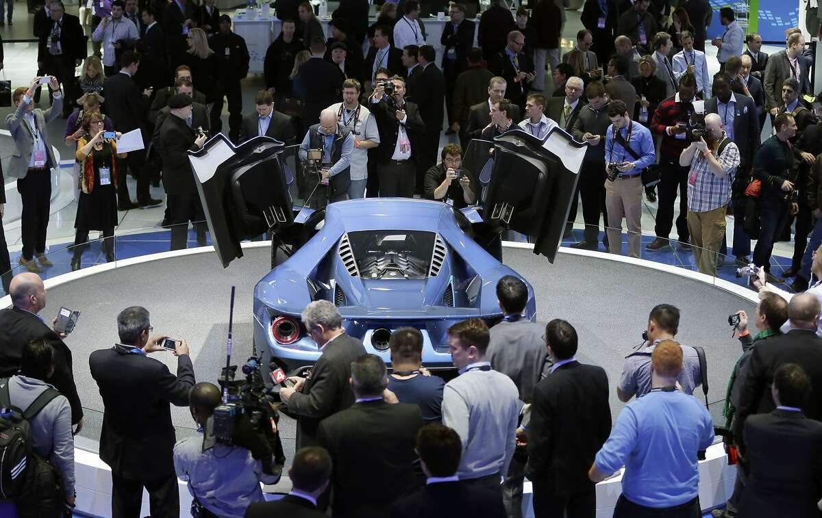 Journalists look over the Ford GT at the North American International Auto Show, Monday, Jan. 12, 2015 in Detroit. (AP Photo/Carlos Osorio)